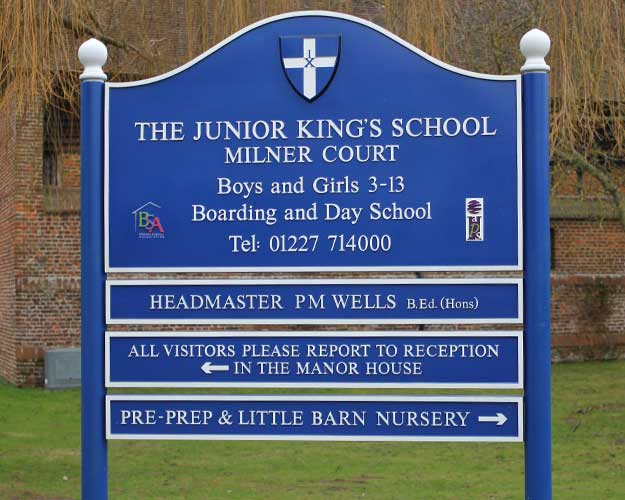 School entrance sign with 3 separate panels below the main sign to allow for changes in information